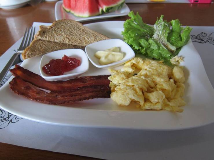 Americano. Slices of toasts with Strawberry jam and fresh butter. Strips of bacon with scrambled eggs.